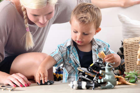 Mother and child playing with toy cars Stock Photo
