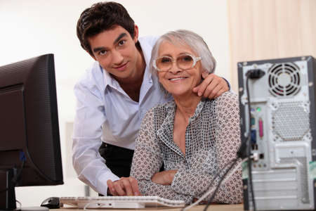 use computer: Young man helping an elderly lady use a computer Stock Photo