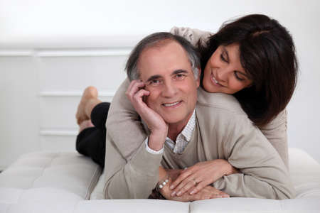 2 50: mature couple lying in bed showing their affection
