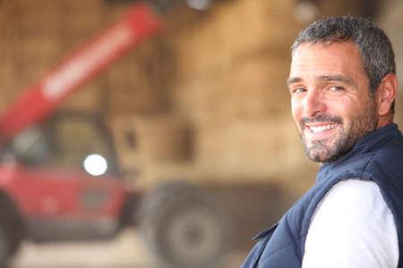 agricultor: Farmer se par� frente a fianzas de heno