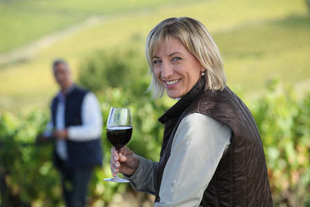 winemaker: Woman standing in vine rows with glass of wine