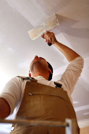 laborious: Man putting up a plasterboard ceiling