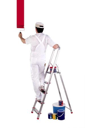 Schilder staande op een ladder