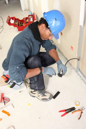 skilled labour: Electrician wiring a building