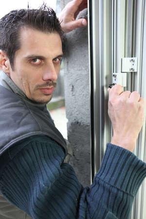 double glazing: Man fitting a window lock