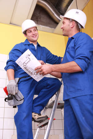 Ventilation: Two electrician repairing ceiling