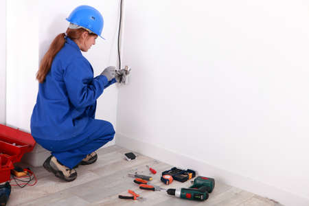 Young woman wiring a plug socket photo