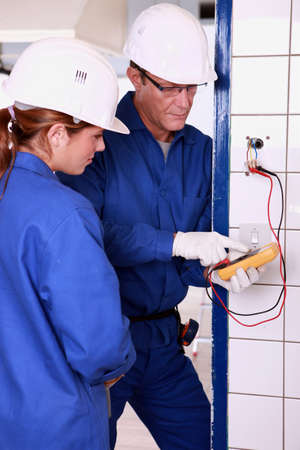 Electrician with female apprentice photo