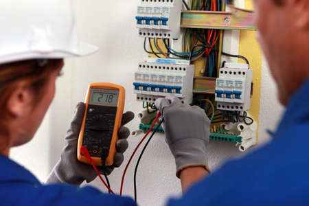 apprentice: electrician and his apprentice working on a fuse board