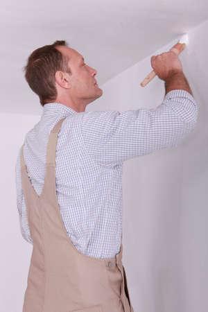 decorando: Hombre pintando una habitaci�n blanca Foto de archivo