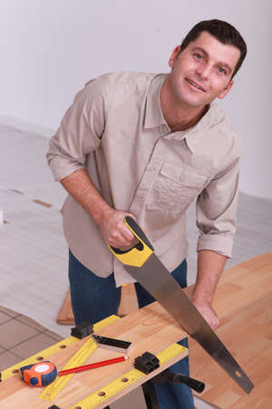 workbench: Man sawing wooden floorboards Stock Photo