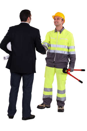 Architect and construction worker shaking hands photo