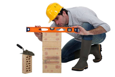 bending over: Tradesman using a spirit level Stock Photo