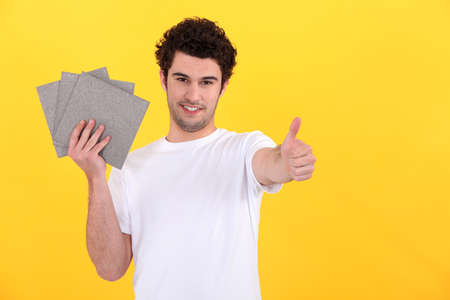 Man holding tiles on yellow background photo