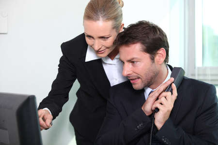 Businessman and woman looking at computer photo