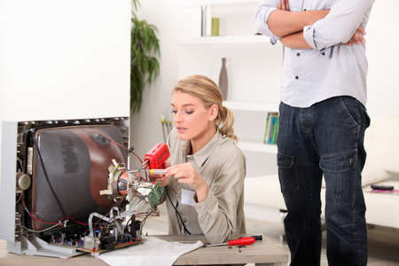 cathode ray tube: a female technician repairing a television