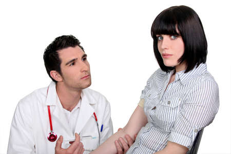 supplicate: Doctor kneeling by a female patient Stock Photo
