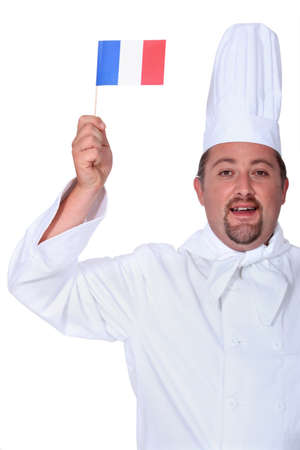 portly: Chef holding miniature French flag Stock Photo