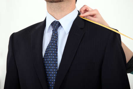 measured: Businessman being measured for a suit Stock Photo