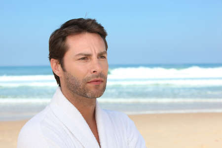 toweling: Distracted man standing on the beach in a bathrobe