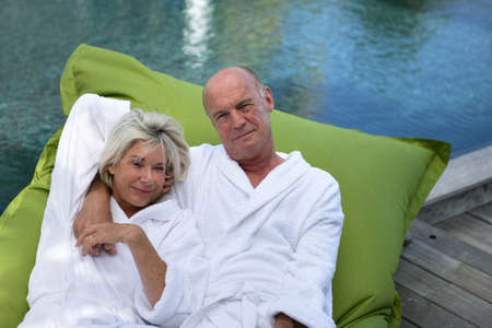 70 year old man: Elderly couple lying on inflatable mattress on a pool deck Stock Photo