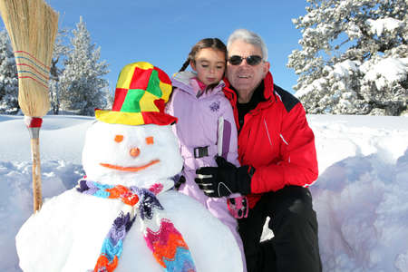Father and daughter building snowman together photo