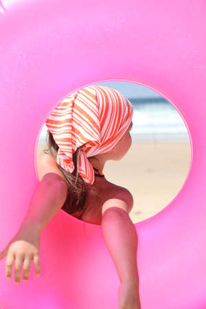rubber ring: Little girl at the beach holding rubber ring