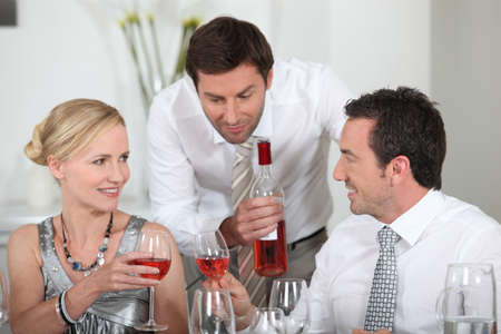 matchmaking: Man serving rose wine at a dinner party Stock Photo