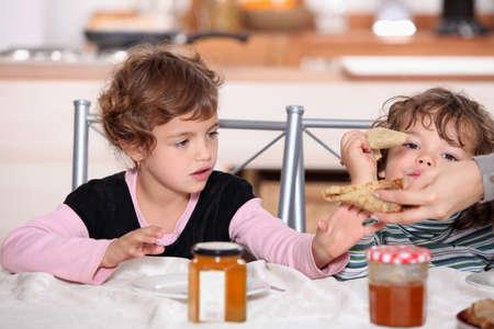 Two children eating breakfast Stock Photo - 11382873