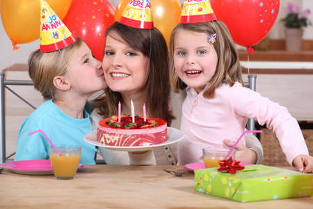 children celebration: Mum and kids with birthday cake Stock Photo