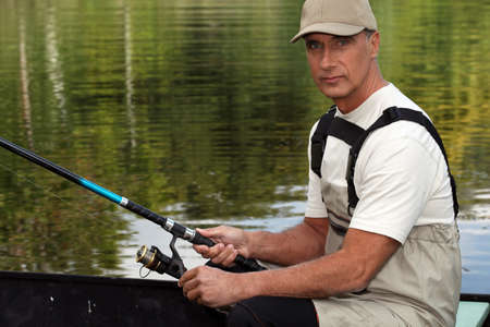 impermeable: 45 years old man on a boat and fishing