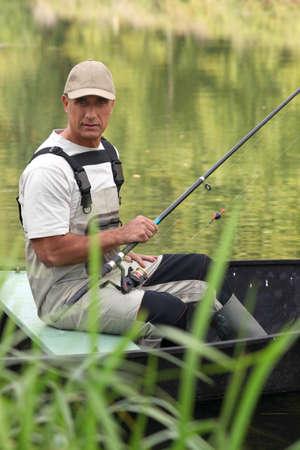 waders: Hombre pescando en una barca en un r�o