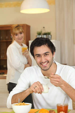 Happy man eating yoghurt for breakfast photo