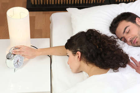 Woman in bed reaching for alarm clock photo