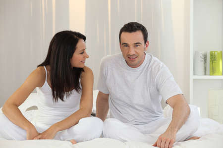 Couple in white sitting in bed photo