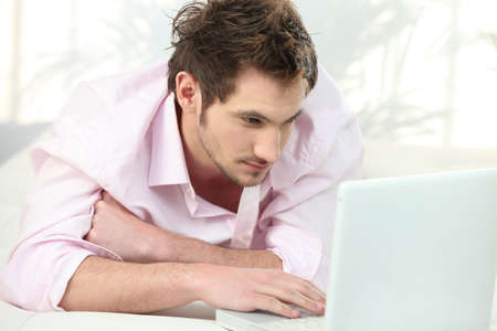 homework student: Young man lying in front of laptop Stock Photo
