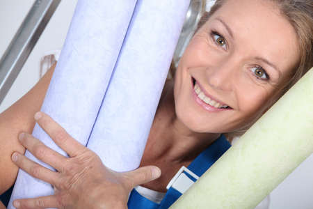 30 34 years: Woman with rolls of wallpaper Stock Photo