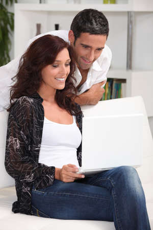 Couple sat at home looking at laptop screen photo