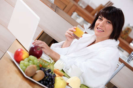 workplace wellness: Woman using a laptop while eating a fruity breakfast Stock Photo