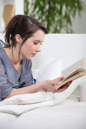interested: A young brunette reading a book. Stock Photo