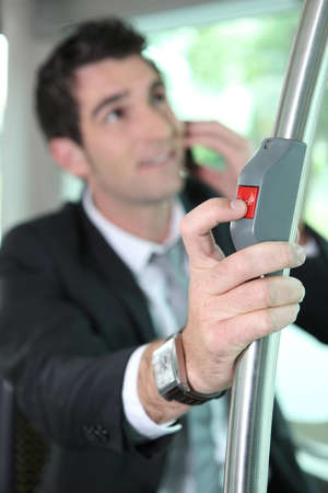 going up: Businessman pressing button on bus