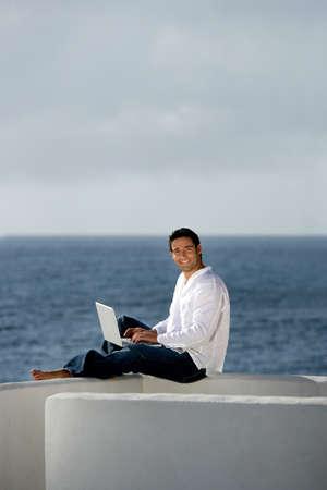 outwork: El hombre con el ordenador port�til en una terraza Foto de archivo