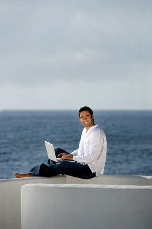 outwork: Man with laptop computer on a terrace
