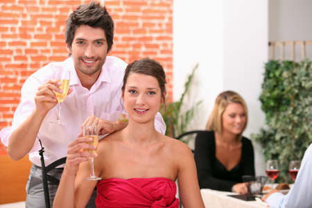 Couple holding champagne flutes in restaurant Stock Photo - 11382630