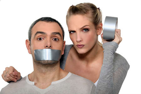 censorship: Woman taping-up mans mouth