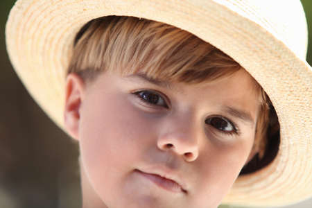 well behaved: little boy wearing a straw hat Stock Photo