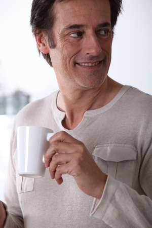 50 55: Man smiling with a cup of tea.