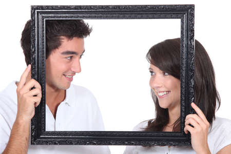 16 19 years: Young couple behind photo frame Stock Photo