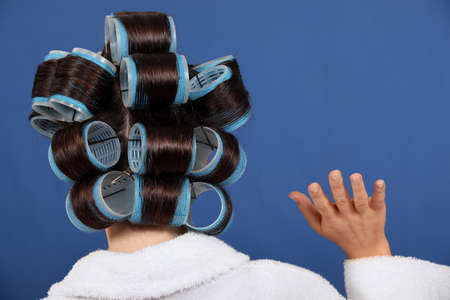 parting off: Back view of a woman wearing rollers and waving