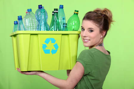separate: Woman recycling crate of plastic bottles